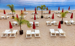 Empty beach with white sunbeds and red umbrellas. Mediterranean beach with white sunbeds and red umbrellas Stock Image