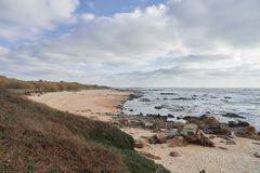 Empty beach on a winter afternoon. Empty rocky beach of Labruge in portugal on a winter afternoon, with the clouds covering the sand and the wild vegetation that stock image