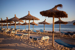 Empty beaxh with straw umbrellas on sunrise. In Spain, Mallorca Royalty Free Stock Photo