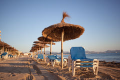 Empty beaxh with straw umbrellas on sunrise. In Spain, Mallorca Royalty Free Stock Photos
