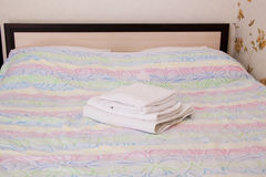 An empty bed in a hotel room. Empty bed with towels in hotel room Royalty Free Stock Photo