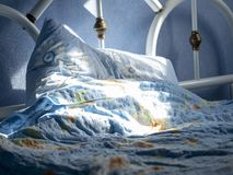 Empty bed lit by the sun. Blue room in which there is an empty bed lit up by the sun royalty free stock images