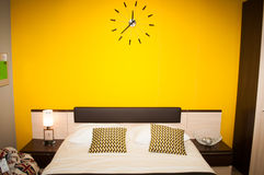 Empty bed with pillows on a background of yellow wall Stock Image