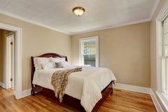 Empty bedroom interior with white bedding and hardwood floor. Stock Image