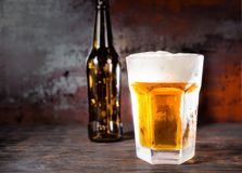 Empty beer bottle next to glass with a light beer and a head of. Foam on old dark desk. Drink and beverages concept Stock Images