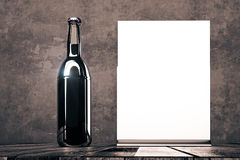 Empty beer bottle and poster Royalty Free Stock Photos