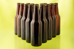 Empty beer bottles in front of green Stock Photo