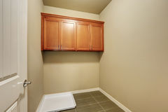 Empty beige laundry room with tile floor. Stock Photos
