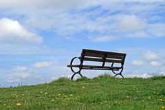 Empty bench. On grassy hill with blue sky and clouds stock image