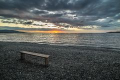 Empty bench on beach at sunset Royalty Free Stock Photo