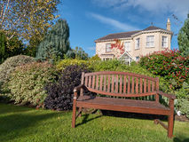 An empty bench before a beautiful manor house Royalty Free Stock Photo