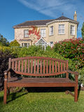 An empty bench before a beautiful manor house. An empty bench in a quiet and restful garden on a sunny day in Ireland Royalty Free Stock Photo