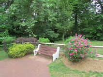 Empty bench at Butterfly Garden in Roosevelt Park, Edison, NJ, USA. Г. Stock Photos