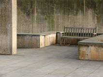 Empty Bench in Concrete Garden. An empty wooden bench in a weathered concrete garden Royalty Free Stock Photos