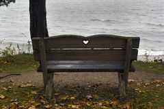 Empty bench facing a cold looking lake. royalty free stock photography