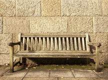 Empty bench. In front of a stone wall with space for text Stock Photos