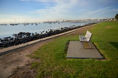 An empty bench on grass by the waters edge. An empty bench on grass by the waters edge in the inspiring bright morning sun with a gorgeous view of boats and Royalty Free Stock Image