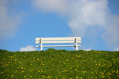Empty bench on green dike Royalty Free Stock Photos
