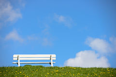 Empty bench on green dike Stock Photos