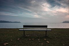 An empty bench by the lake at sunset. An empty bench by the lake of Varese at sunset Royalty Free Stock Images