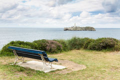 Empty bench and lighthouse in Santander Stock Photography
