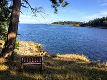 An empty bench looking out at the beautiful ocean along the coast of British Columbia and the Gulf Islands. stock photos