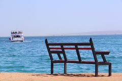 Empty bench near sea and shipped ship. Loneliness. Departure of ship. Bench near beach. Unjustified expectations. Exotic relaxation. Holiday concept stock photography