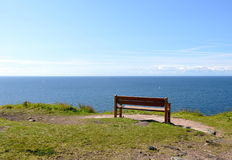 Empty bench near the sea staying lonely Stock Images