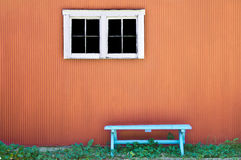 Empty bench on orange wall Stock Photos