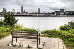 Empty bench overlooking the Antwerp skyline with the schelde river. An empty bench overlooking the skyline of Antwerp, Belgium with the cathedral and the Schelde Royalty Free Stock Images