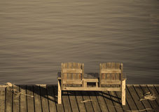 Empty bench overlooking the water in a tranquil and relaxing sce Stock Images