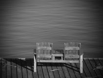 Empty bench overlooking the water in a tranquil scene Royalty Free Stock Images