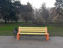 An empty bench in the park, painted in yellow and red royalty free stock image