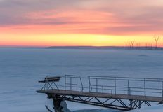 Bench on the pier on the background of pink sunset royalty free stock photography