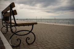 Empty bench on the promenade in cloudy weather. Empty wrought iron bench with wooden seat and back on a deserted promenade overlooking the sea in cloudy weather Stock Image