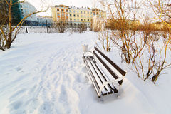 An empty bench in the snow-covered city park Royalty Free Stock Images