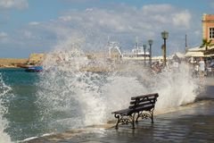 An empty bench stands on the edge of the embankment of Chania about which waves and a lot of splashes beat stock image