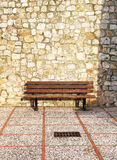 An empty bench, stone blocks background Stock Image