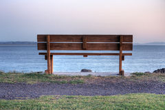 An empty bench at sunrise stock photo