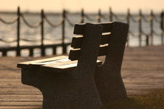 Empty Bench in a Sunset. A warmly lit bench during a sunset on a pier royalty free stock photo