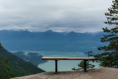 Empty bench on top of a cliff overlooking the Howe Sound. Stock Photo
