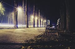 Empty bench on walk at night Royalty Free Stock Photography