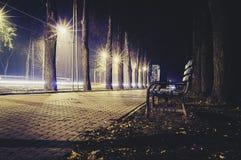 Empty bench on walk at night