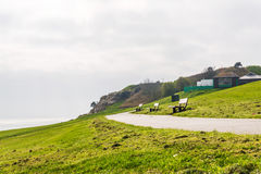 Empty benches on the ocean bay, view on the horizon, green gras. S, hill royalty free stock image