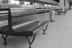 Empty benches at railway station. Freight train in the background stock image
