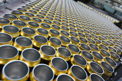 Empty beverage cans on the conveyor belt Stock Photos