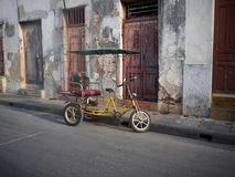 Empty Bicitaxi Camaguey Cuba. Bicitaxi parked in street in Cuba.  Yellow bike with red seat and uncover.  The homes in the street are old decayed and grungy Stock Images