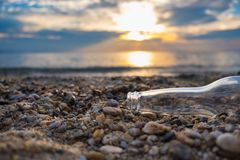 Empty bier bottle laying on the pebble beach with sunset sky in the background. royalty free stock image