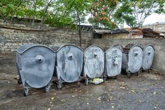 Empty big gray garbage containers in a row on a sunny urban street. A row of gray iron garbage cans on the street - Image royalty free stock images