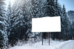 Empty billboard for advertising poster, on the background of snowy fir-trees. Winter season in a mountainous area. Empty billboard for advertising poster, on Stock Image